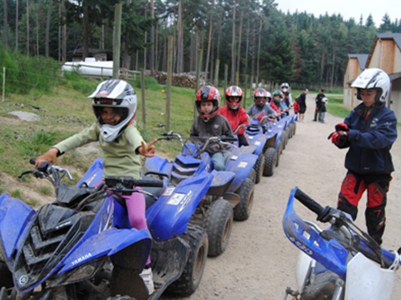groupe d'enfants conduisant un quad les uns derrière les autres en stage sportif