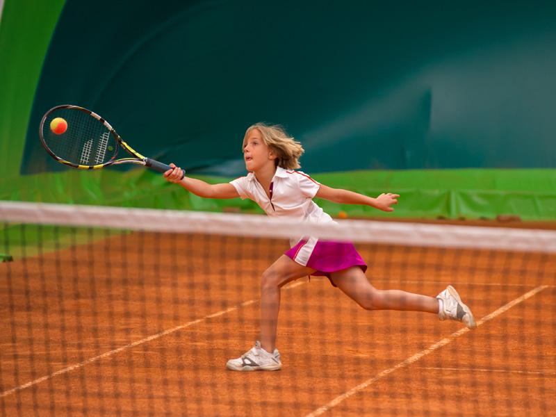 jeune fille participant à un stage sportif de tennis cet été