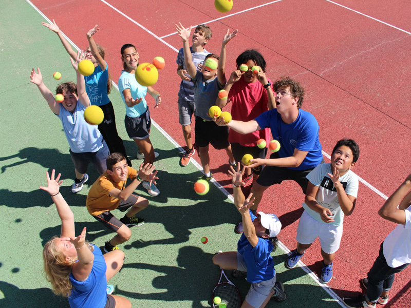 groupe de jeunes en stage sportif jouant au tennis cet été