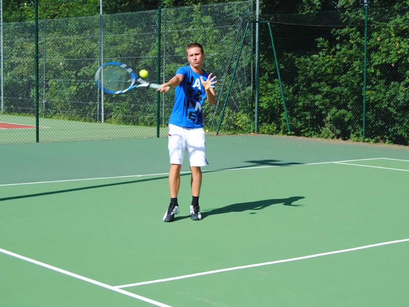 Adolescente jouant au tennis cet été durant un stage sportif