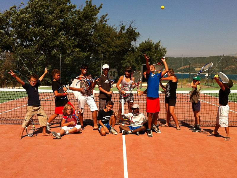 groupe d'enfants et ados jouant au tennis cet été en stage sportif