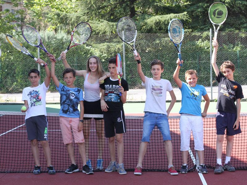 groupe d'enfants en colonie de vacances jouant au tennis