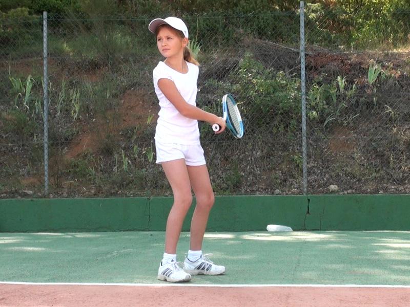 fillette jouant au tennis en stage sportif pour se perfectionner cet été