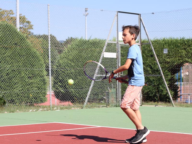 enfant jouant au tennis en stage sportif