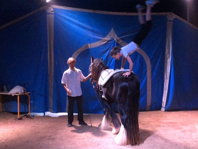 Enfant qui fait des acrobaties sur un cheval en colonie de vacances