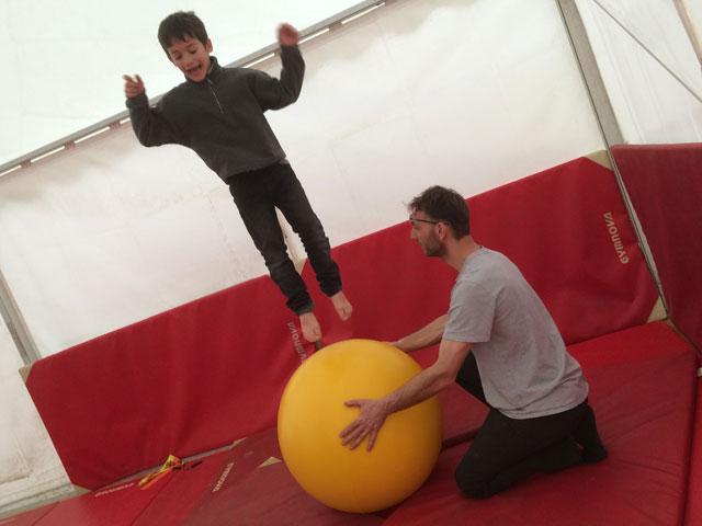 Enfant qui pratique le cirque sous l'œil vigilent de l'animateur de colonie de vacances