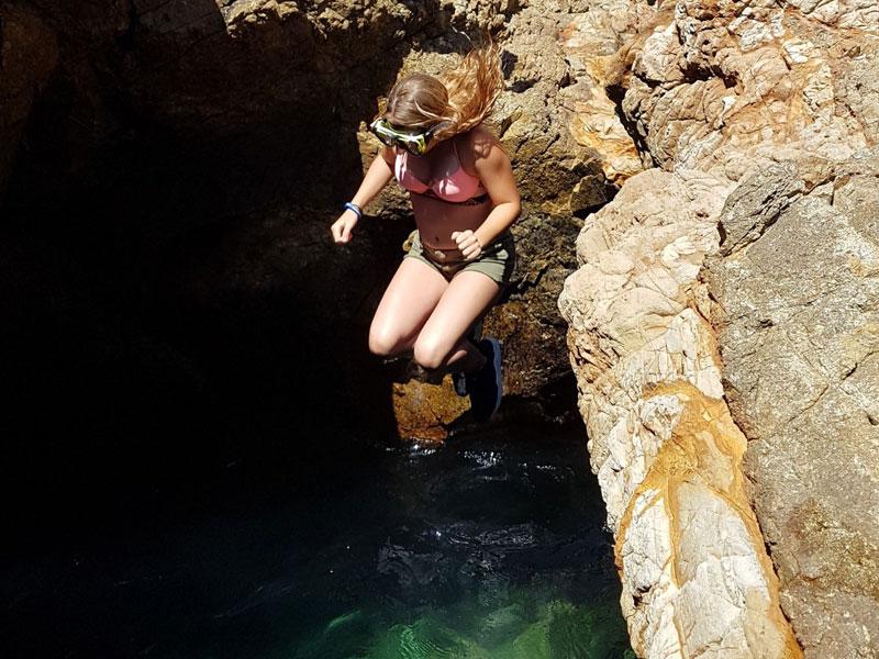 Jeune fille qui saute dans l'eau en Corse