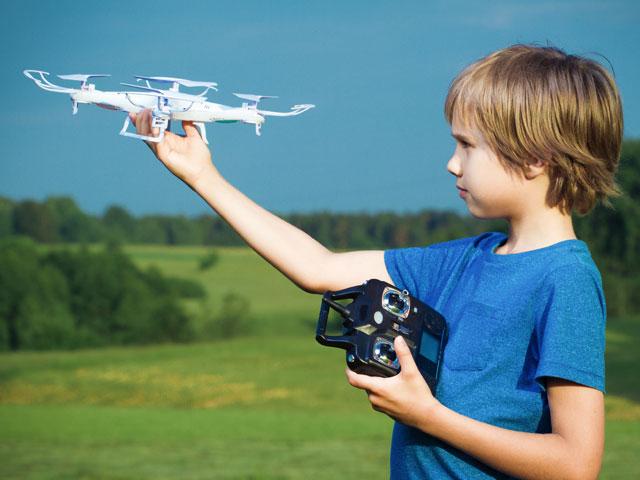Enfant apprenant à faire voler un drone en colonie de vacances à la campagne