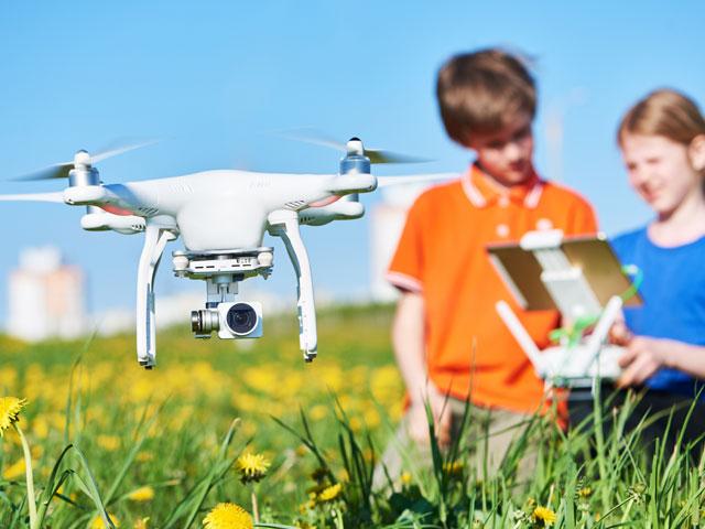 enfants apprenant ensemble à piloter le drone en colonie de vacances