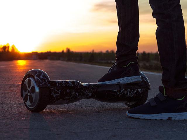 Adolescent faisant de l'hoverboard en fin de journée en colonie de vacances multiactivités cet été