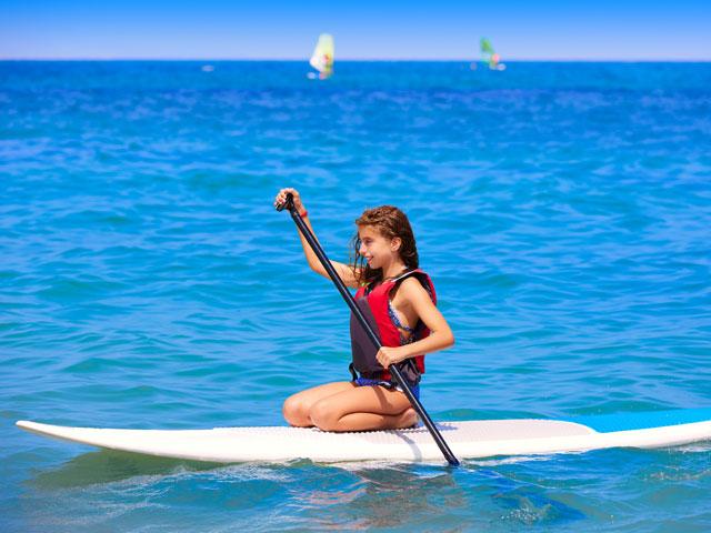 Adolescente sur sa planche de paddle en colonie de vacances en corse cet été