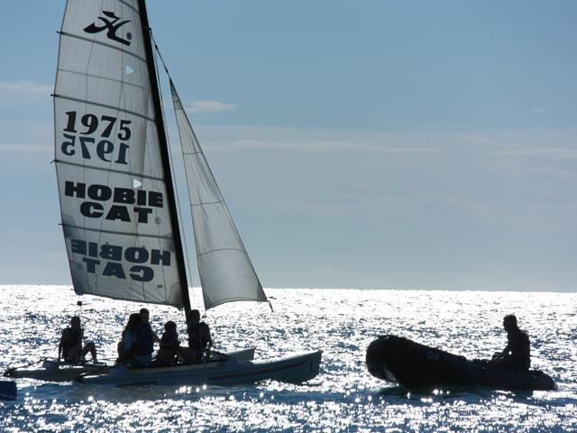 Enfants faisant du bateau à voile à la mer en colonie de vacances en corse