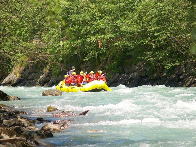 Groupe d'enfants et ados faisant du rafting en colonie de vacances à la montagne été