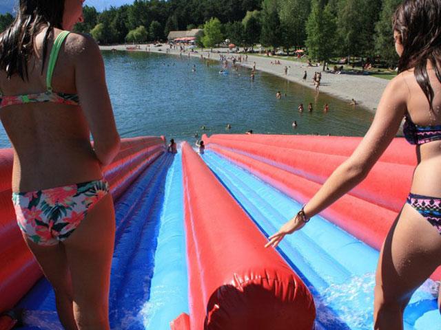 Jeunes filles faisant des glissades sur un toboggan gonflable à la montagne en été