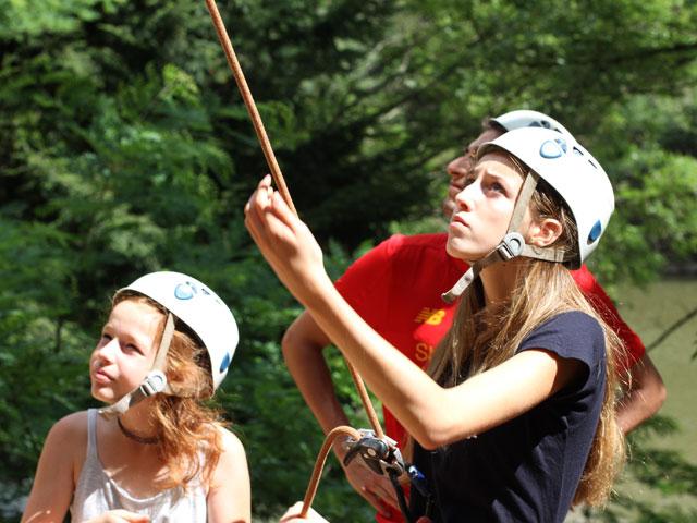 Fillette et adolescente pratiquant l'escalade en colonie de vacances à la montagne