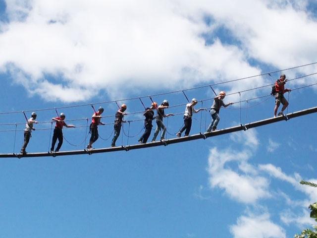 Groupe d'enfants sur un pont dans les airs en colonie via ferrata