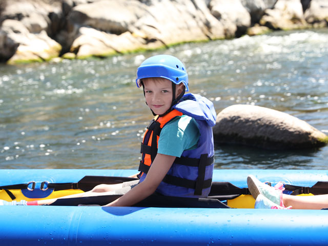 Enfant faisant du canoe kayak en colonie de vacances à la montagne