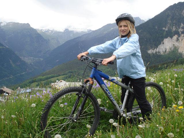Jeune fille faisant du vélo en colonie de vacances à la montagne