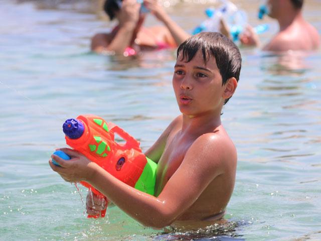 Enfant jouant au pistolet à eau en colonie de vacances