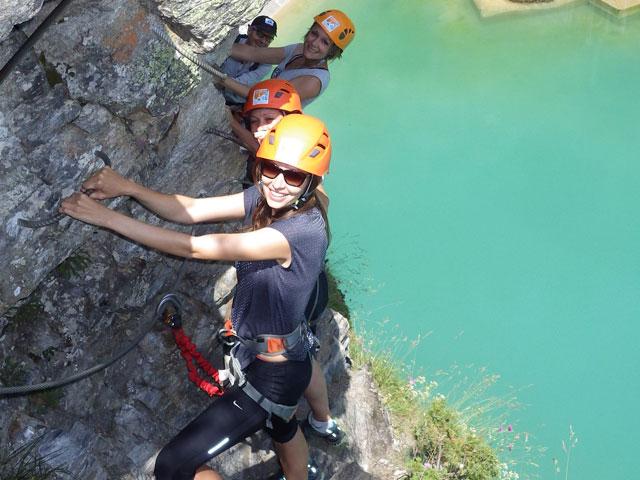 Adolescents faisant de la via ferrata en colonie de vacances à la montagne