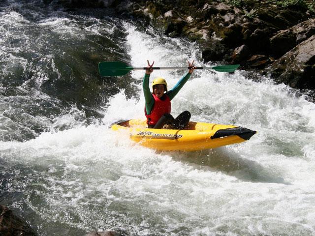 Ado faisant du canoe kayak en colonie de vacances d'été à la montagne