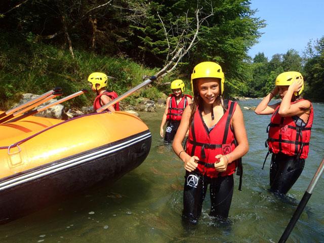 Adolescents dans l'eau faisant du canoe kayak en colonie de vacances