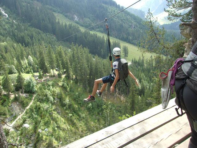 Enfants faisant de la tyrolienne en montagne en colo été