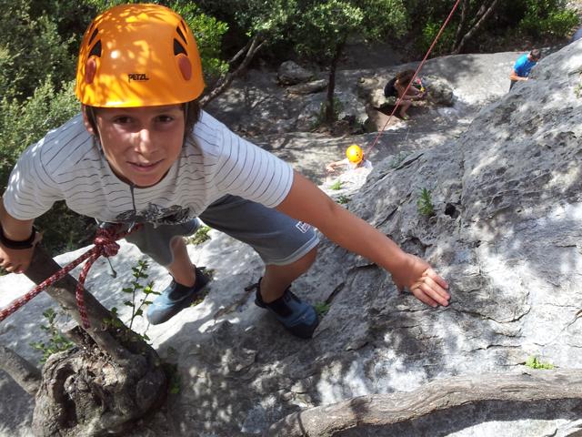 Enfant faisant de l'escalade en colonie de vacances d'été à la montagne