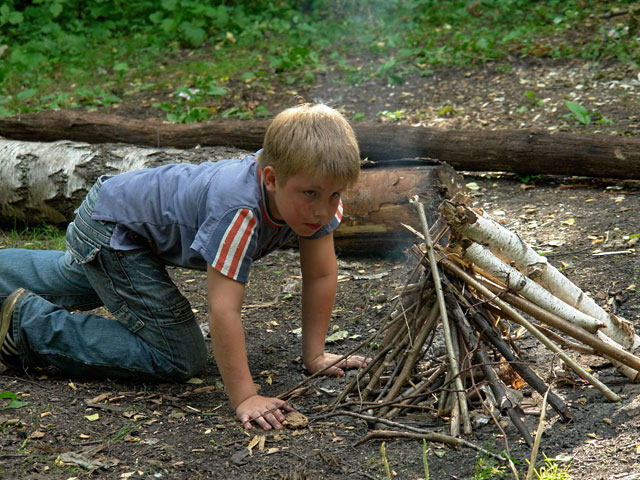 Enfant apprenant à faire du feu en colonie de vacances à la mpntage