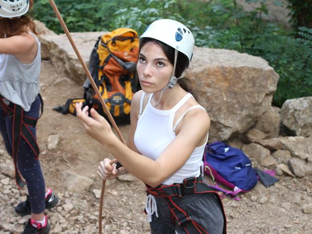 Jeune fille faisant de l'escalade en colonie de vaances à la montagne