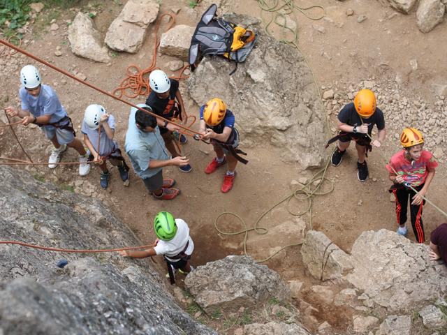 Groupe d'enfants vus de haut s'équipant pour faire de l'escalade en colonie de vacances été