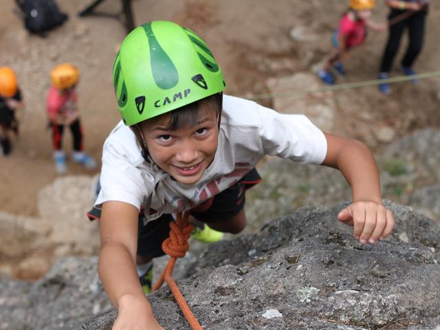 Garçon pratiquant l'escalade en colonie de vacances à la montagne cet été