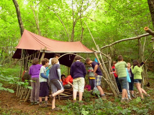 Groupe d'enfants construisant une cabane en colonie de vacances d'été