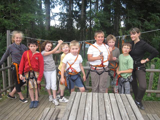 Groupe de jeunes enfants équipés pour faire de l'accrobranche en colonie de vacances
