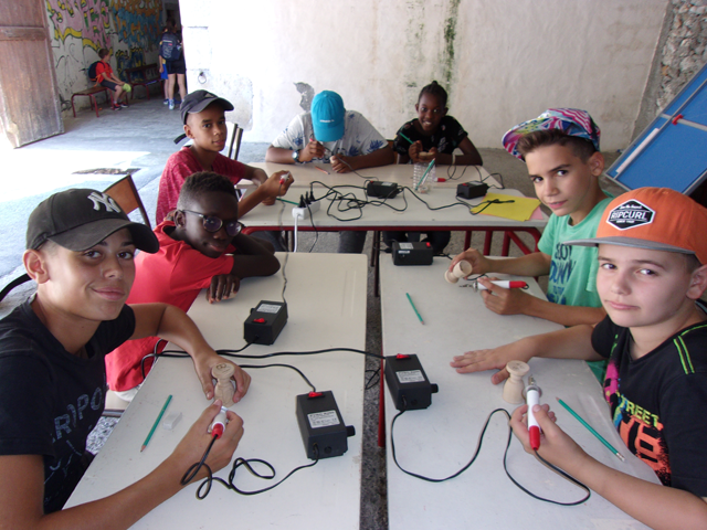 Groupe d'enfants en colonie de vacances apprenant à faire de la pyrogravure