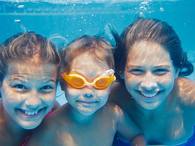 Trois enfants sous l'eau dans la piscine en colonie de vacances d'ét
