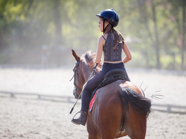 Jeune fille en balade à cheval en colo équitation été