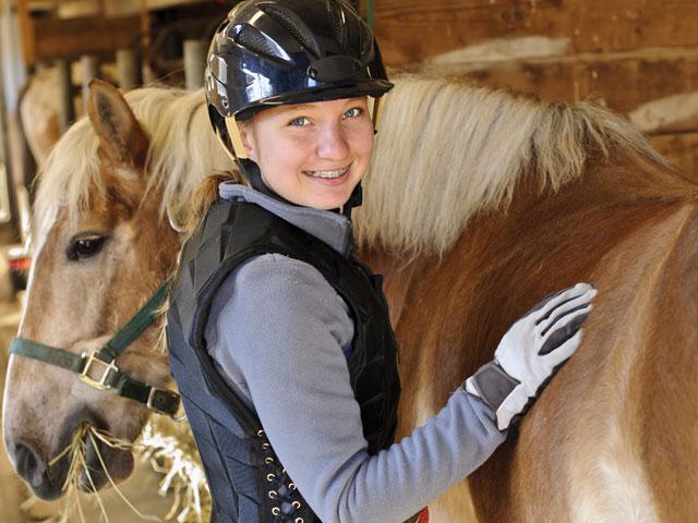 Jeune fille brossant son cheval en colonie de vacances d'été à la montagne