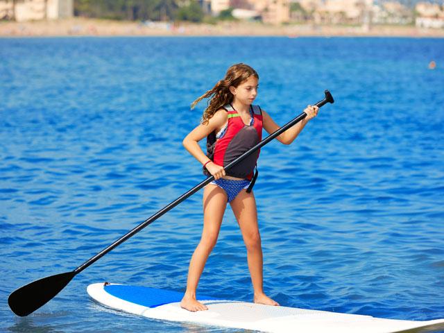 Fille sur un standup paddle en colonie de vacances d'été