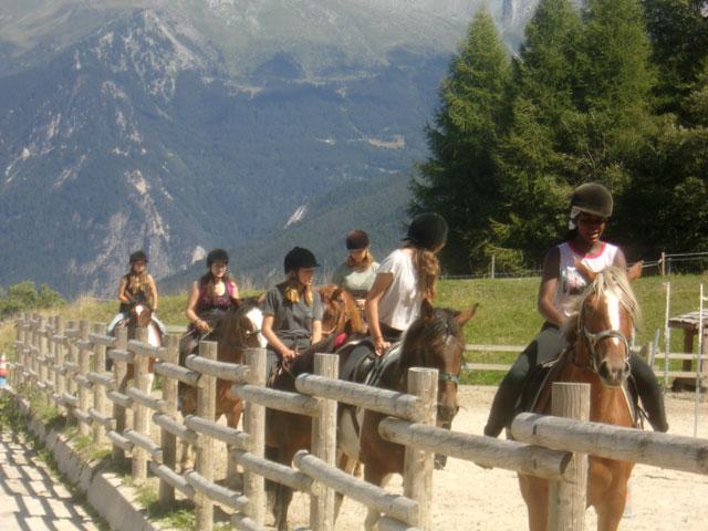 Groupe d'adolescents à cheval en colonie de vacances équitation à la montagne été