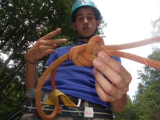 Ado qui apprend à faire un noeud d'escalade en colo