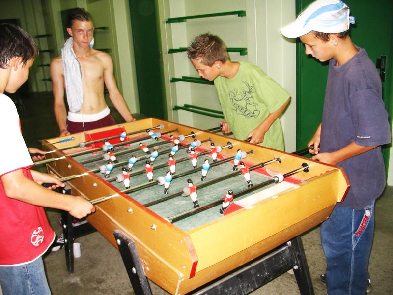 Groupe d'ados jouant au babyfoot en colonie de vacances
