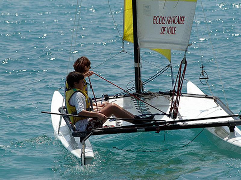 Enfant sur un bateau à voile en colonie de vacances