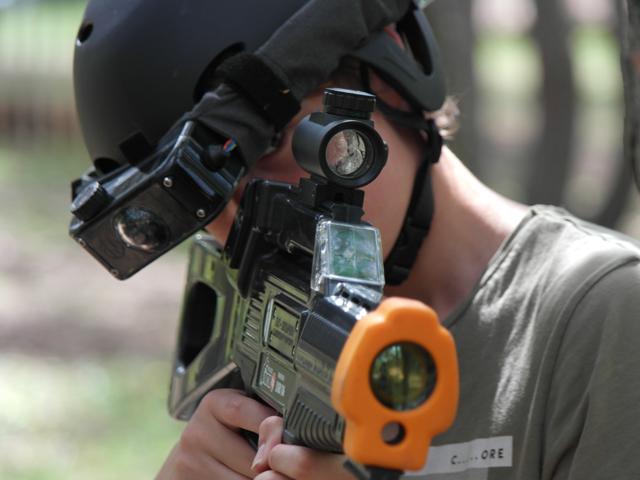 Portrait d'un enfant faisant du laser game extérieur en colo
