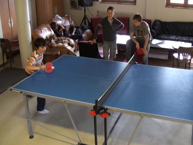 Enfants jouant au ping pong en colo