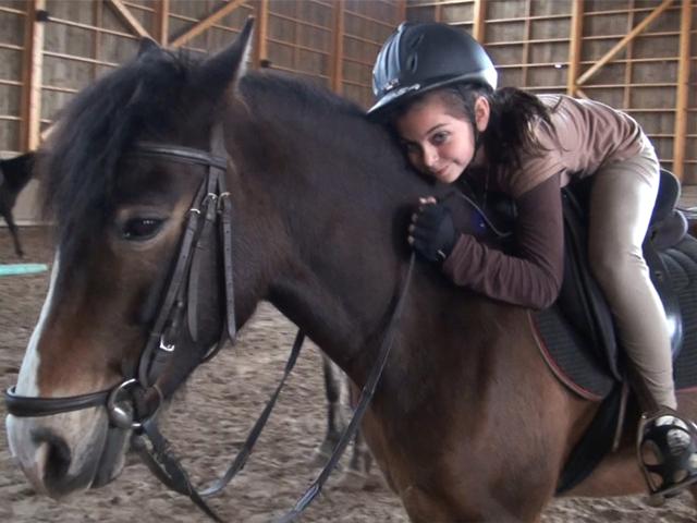 Fillette faisant un calin à son cheval en colonie de vacances