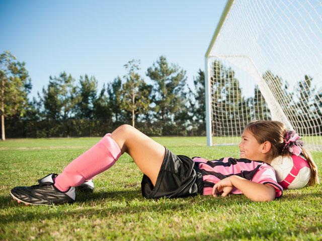 Jeune fille sur la pelouse de football du stage sportif cet été