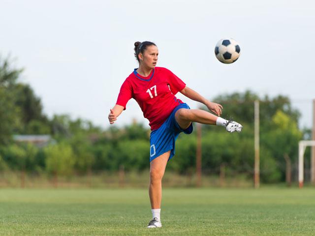 Jeune fille faisant du football en stage sportif cet été