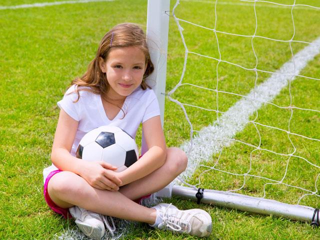 Fillette sur le terrain de football du stage de foot féminin cet été