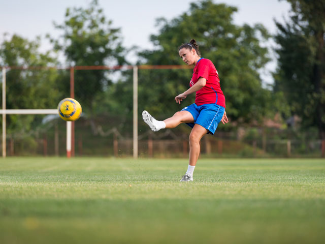 Adolescente faisant du football cet été en stage sportif